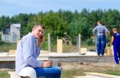 Junger Erbauer, der auf seinem Mobile plaudert Stockfotografie