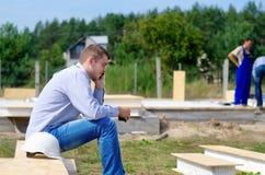 Junger Erbauer, der auf seinem Mobile plaudert Stockbild