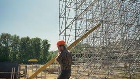 Junger Erbauer im Sturzhelm, der die Schwermetallplanke, arbeitend nahe enormer Installation auf Strohfeld trägt stock footage