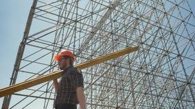 Junger Erbauer im Sturzhelm, der die Schwermetallplanke, arbeitend nahe enormer Installation trägt stock video footage