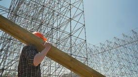 Junger Erbauer im Sturzhelm, der die Schwermetallplanke, arbeitend nahe enormer Metallinstallation überträgt stock video footage