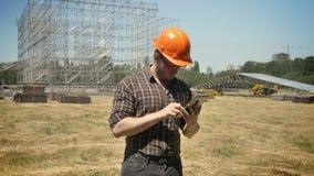 Junger Erbauer im Sturzhelm, der mit Tablette auf Strohfeld, Metallinstallation auf dem Hintergrund, konzentriert steht stock video