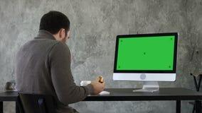 Junger erdrosselnder Mann beim Essen und Aufpassen etwas auf dem Computer im Büro Grüne Schirm-Modell-Anzeige stock video footage