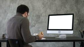 Junger erdrosselnder Mann beim Essen und Aufpassen etwas auf dem Computer im Büro Weiße Bildschirmanzeige stock video footage