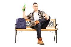 Junger erfüllter Student, der auf einer Bank und einem trinkenden Bier sitzt Stockfotos