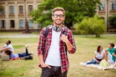 Junger erfolgreicher blonder nerdy Student steht mit Rucksack a Lizenzfreie Stockfotografie