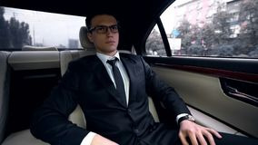 Junger erfolgreicher Geschäftsmann, der zum Treffen im Luxusauto, Verkehr in der Stadt geht stockbilder