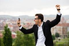 Junger erfolgreicher Unternehmer, der Smartphone schaut lizenzfreies stockfoto