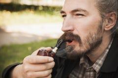 Junger ernster asiatischer bärtiger Mann raucht Lizenzfreies Stockbild