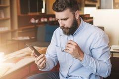 Junger ernster attraktiver bärtiger Geschäftsmann im blauen Hemd sitzt auf Sofa im Café und hält Gläser und benutzt Smartphone Stockfoto