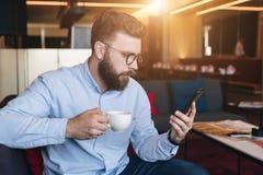 Junger ernster attraktiver bärtiger Geschäftsmann im blauen Hemd und in den Gläsern sitzt auf Sofa im Café, trinkt Kaffee und Geb Stockfotos