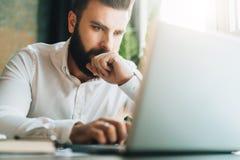 Junger ernster bärtiger Geschäftsmann, der bei Tisch im Büro sitzt und Laptop verwendet Mann arbeitet an Computer, überprüft E-Ma Stockfotografie