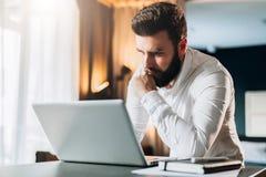 Junger ernster bärtiger Geschäftsmann, der im Büro nahe Tabelle steht und Laptop verwendet Mann arbeitet an Computer, überprüft E Stockbild