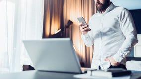 Junger ernster bärtiger Geschäftsmann, der nahe Tabelle vor Laptop, unter Verwendung des Smartphone steht Mann überprüft E-Mail Lizenzfreies Stockbild