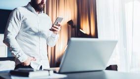 Junger ernster bärtiger Geschäftsmann, der nahe Tabelle vor Laptop, unter Verwendung des Smartphone steht Mann überprüft E-Mail Lizenzfreie Stockfotografie