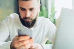 Junger ernster bärtiger Geschäftsmann sitzt im Büro bei Tisch nahe Fenster, benutzt Smartphone Mann überprüft E-Mail Stockfoto