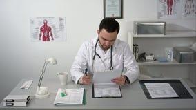 Junger ernster Doktor zerstört die Dokumente, die im Ärztlichen Dienst mit Ordner sitzen stock video footage