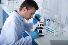 Junger ernster Forscher, der durch das Mikroskop sitzt und mit ihm arbeitet stockfotografie