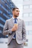 Junger ernster Geschäftsmann mit Papierschale draußen Lizenzfreie Stockfotos