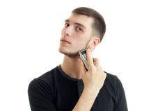 Junger ernster Kerl im schwarzen Hemd rasiert seinen Bart Lizenzfreie Stockfotos