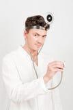 Junger ernster männlicher Doktor mit einem Stethoskop Lizenzfreie Stockfotos