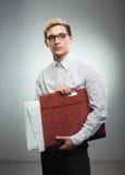 Junger ernster Mann in den Gläsern mit einem Zeichnungsordner in den Händen Stockbilder