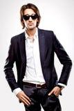 Junger ernster Mann in den Sonnenbrillen und in der Klage Stockfotos
