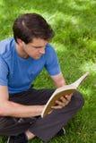 Junger ernster Mann, der mit überkreuzten Beinen beim Lesen eines Buches sitzt Stockbilder