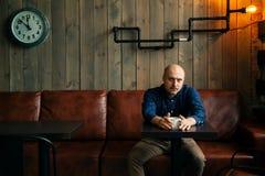 Junger ernster moderner Mann, der allein in Dachboden-angeredetem Café sitzt stockfotos