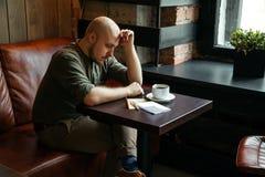 Junger ernster moderner Mann, der allein in Dachboden-angeredetem Café sitzt Stockfoto
