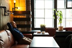 Junger ernster moderner Mann, der allein in Dachboden-angeredetem Café sitzt Stockbilder
