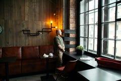 Junger ernster moderner Mann, der allein in Dachboden-angeredetem Café sitzt Lizenzfreie Stockfotografie