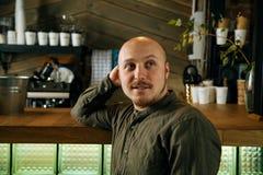 Junger ernster moderner Mann, der allein in Dachboden-angeredetem Café sitzt Lizenzfreies Stockbild