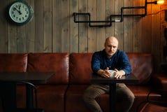 Junger ernster moderner Mann, der allein in Dachboden-angeredetem Café sitzt Stockbild