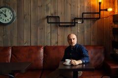 Junger ernster moderner Mann, der allein in Dachboden-angeredetem Café sitzt Stockfotografie