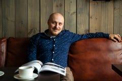 Junger ernster moderner Mann, der allein in Dachboden-angeredetem Café sitzt Lizenzfreie Stockbilder
