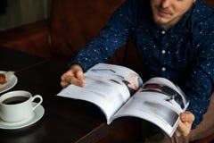 Junger ernster moderner Mann, der allein in Dachboden-angeredetem Café sitzt Lizenzfreies Stockfoto