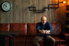 Junger ernster moderner Mann, der allein sitzt Lizenzfreie Stockbilder