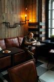 Junger ernster moderner Mann, der allein sitzt Lizenzfreies Stockfoto