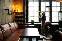 Junger ernster moderner Mann, der allein sitzt Stockbilder