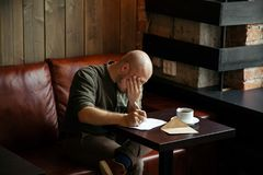 Junger ernster moderner Mann, der allein sitzt und einen Brief schreibt Lizenzfreie Stockbilder
