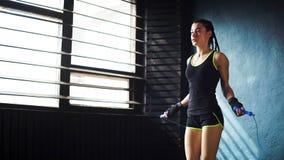 Junger ernster weiblicher Boxer im eingewickelten Handaufwärmen, springend auf Springseil im freien Raum der Turnhalle stockfotografie