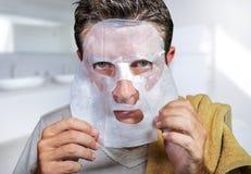 Junger erschrockener und ?berraschter Mann zu Hause unter Verwendung der Sch?nheitspapier-Gesichtsmaske, die die alternde Gesicht stockfotos
