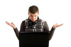Junger erstaunter Geschäftsmann, der an einem Laptop arbeitet Stockbilder