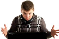 Junger erstaunter Geschäftsmann, der an einem Laptop arbeitet Lizenzfreie Stockfotos