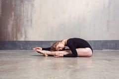 Junger erwachsener Balletttänzer, der Übung beim Sitzen auf f durchführt stockbilder