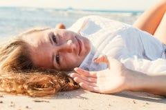 Junger Erwachsener bräunte blonde Mädchenlügen auf dem Sand auf dem Strand nahe lizenzfreies stockfoto