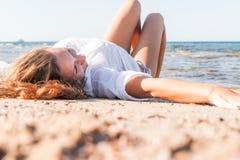 Junger Erwachsener bräunte blonde Mädchenlügen auf dem Sand auf dem Strand nahe stockfoto