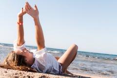 Junger Erwachsener bräunte blonde Mädchenlügen auf dem Sand auf dem Strand nahe stockfotos