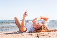 Junger Erwachsener bräunte blonde Mädchenlügen auf dem Sand auf dem Strand nahe stockbild